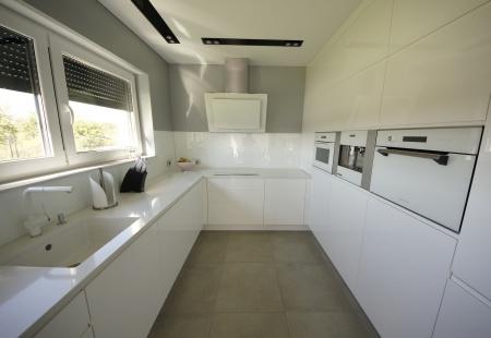 A może by tak całą kuchnię w bieli?  Białe fronty lakierowane w połysku, biały blat z konglomeratu kwarcowego, białe szkło i do tego biały sprzęt AGD...