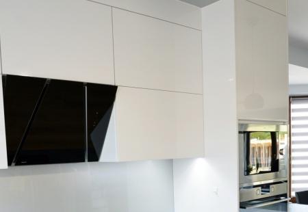 Nowoczesna zabudowa kuchenna w białym połysku, z grafitowymi blatami, ocieplona drewnianą podłogą. Fronty połyskowe z uchwytami krawędziowymi lakierowanymi na biało.