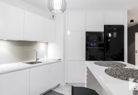 Kuchnia na wymiar z wyspą w realizacji 3TOP. Meble zostały wykonane z MDF lakierowanego w białym kolorze.